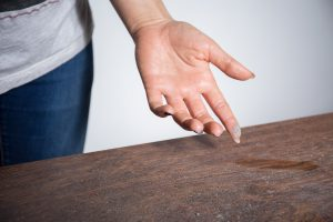 Close-up of dust on woman finger taken from wooden table eliminate dust mites